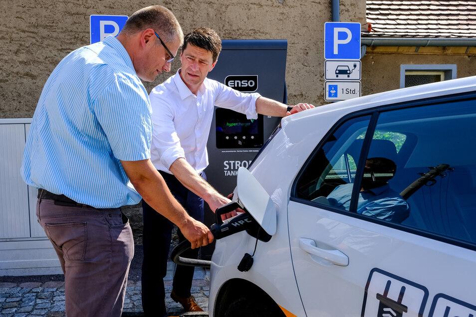 """Gunnar Schneider von der Enso erklärt Bürgermeister Siegfried Zenker (li.), wie er sein geliehenes Elektro-Auto in den nächsten Tagen laden kann. Rund 250 Kilometer weit kommt er mit dem E-Golf ohne zu """"tanken"""". Für zwei Wochen darf er das Auto testen."""