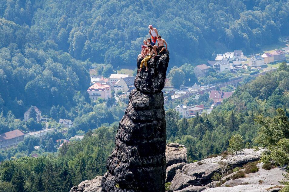 Kletterer sitzen auf der Schrammsteinnadel und schauen ins Elbland hinab.