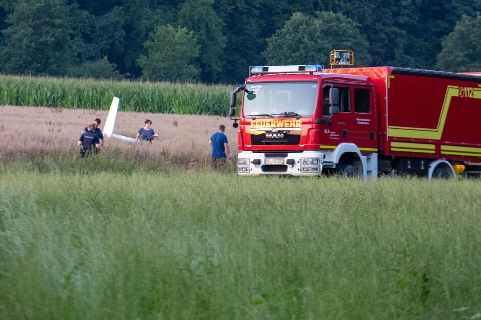 Einsatzkräfte arbeiten an der Absturzstelle von einem Kleinflugzeug in einem Getreidefeld.