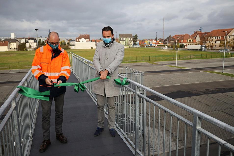 Feralpi-Werksdirektor Christian Dohr (l.) und Riesas Oberbürgermeister Marco Müller (CDU, r.) eröffnen den Parkplatz. Die Wiese im Hintergrund gehört ebenfalls dem Stahlwerk, dort sollen noch Bäume und Sträucher gepflanzt werden.