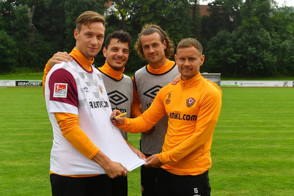 Knippings Mitspieler Philipp Hosiner, Yannick Stark und Chris Löwe (v.l.) unterstützen die Versteigerung und unterschreiben auf dem Trikot. Auch finanziell haben sie sich bereits beteiligt.