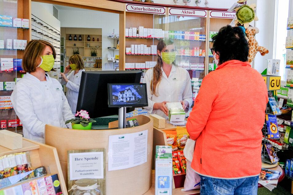 Tragen selbst hinter der Plexiglasscheibe noch Mundschutz – die Mitarbeiterinnen in der Alten Apotheke von Weinböhla.