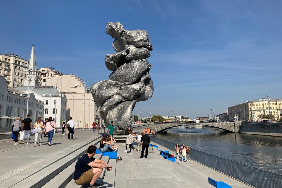 Menschen sitzen neben der Skulptur ·Big Clay #4· des Schweizer Künstlers Urs Fischer in Moskau. (