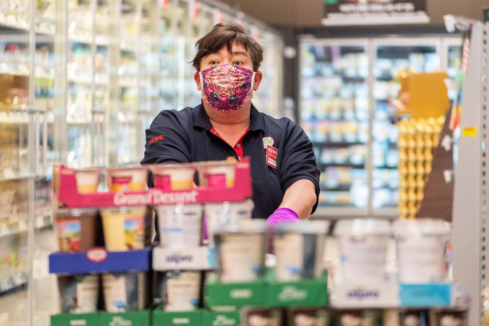 Eine Mitarbeiterin in einem Dresdner Supermarkt trägt eine Schutzmaske, um sich und Kunden vor einer Corona-Infektion zu schützen. Was für Discounter längst zum Alltag gehört, stellt andere Branchen vor Probleme.