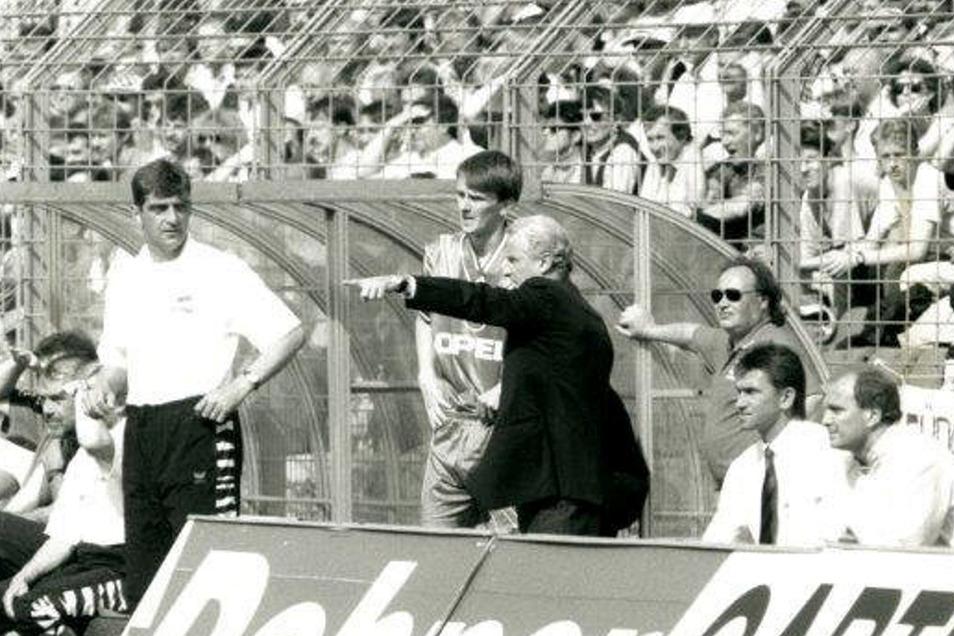 Ralf Minge (l.) schaut skeptisch rüber. Sein Kollege Giovanni Trapattoni kann beim FC Bayern Nationalspieler Dietmar Hamann einwechseln. Dynamo verliert im bislang letzten Bundesliga-Heimspiel der Vereinsgeschichte am 10. Juni 1995 vor 29.253 Zuschauern g