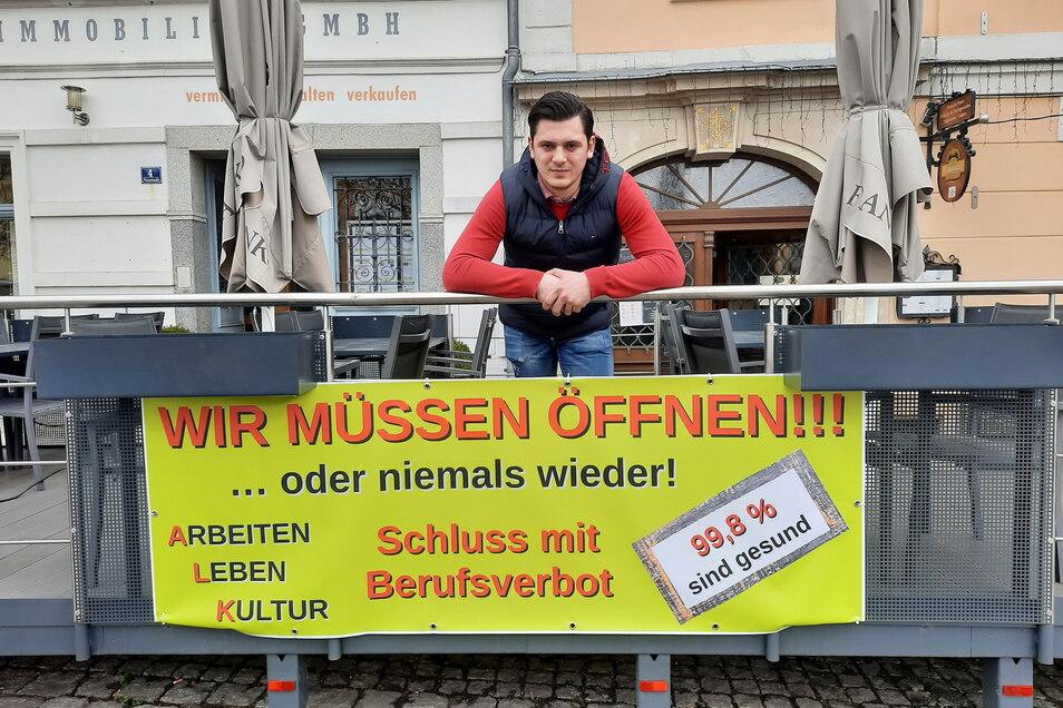 Gjok Karaqi von der Pizzeria Franko auf der Zittauer Neustadt mit dem Protestbanner, das an seinem Biergarten befestigt wurde.