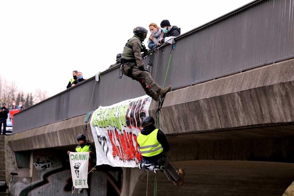Spezialisten der Polizei holen die abgeseilten Klimaschützer von der Brücke.