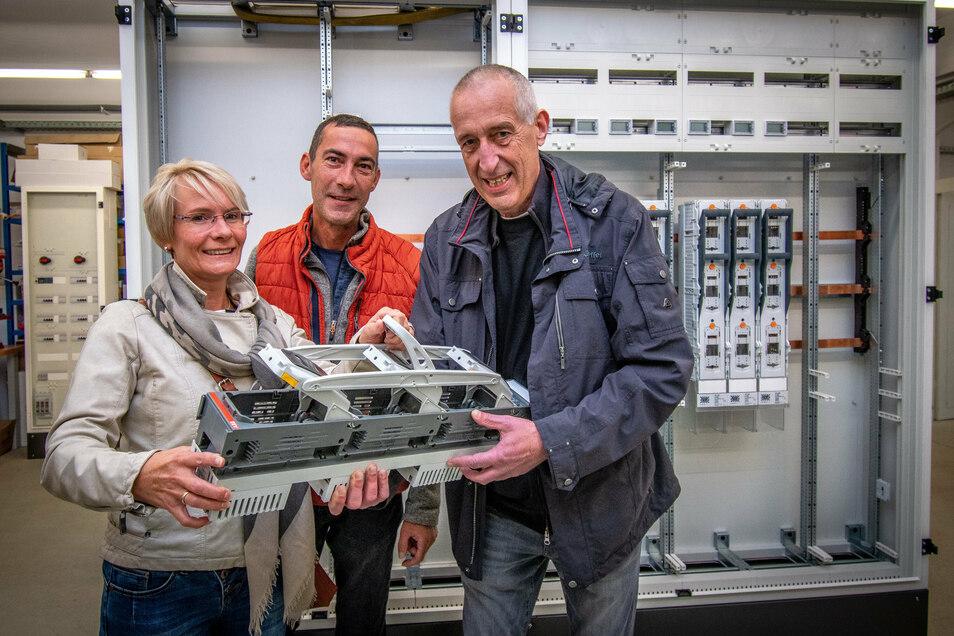 Beim Tag der offenen Tür der Firma EGH Hartha lassen sich Silke und Matthias Stein aus Chemnitz von Projektleiter Thomas Feodorow (von links) einen Sicherungslastentrenner erklären.