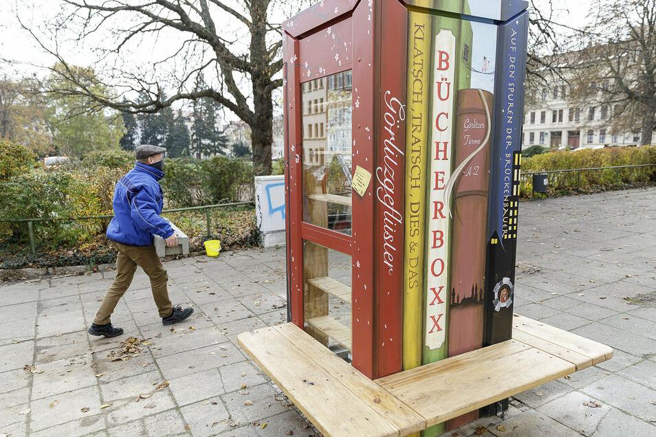 """Frank Israel vom Städtischen Betriebshof baute den Zaun um die """"Bücherboxx"""" ab. Nun ist sie mit Literatur bestückt."""