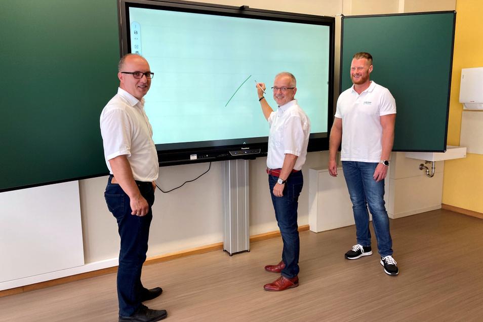 Stefan Skora (Mitte) erfuhr bei seinem Besuch am Lessing- Gymnasium, was so eine digitale Tafel alles kann. Für jede einzelne garantiert der Hersteller 50.000 Betriebsstunden.