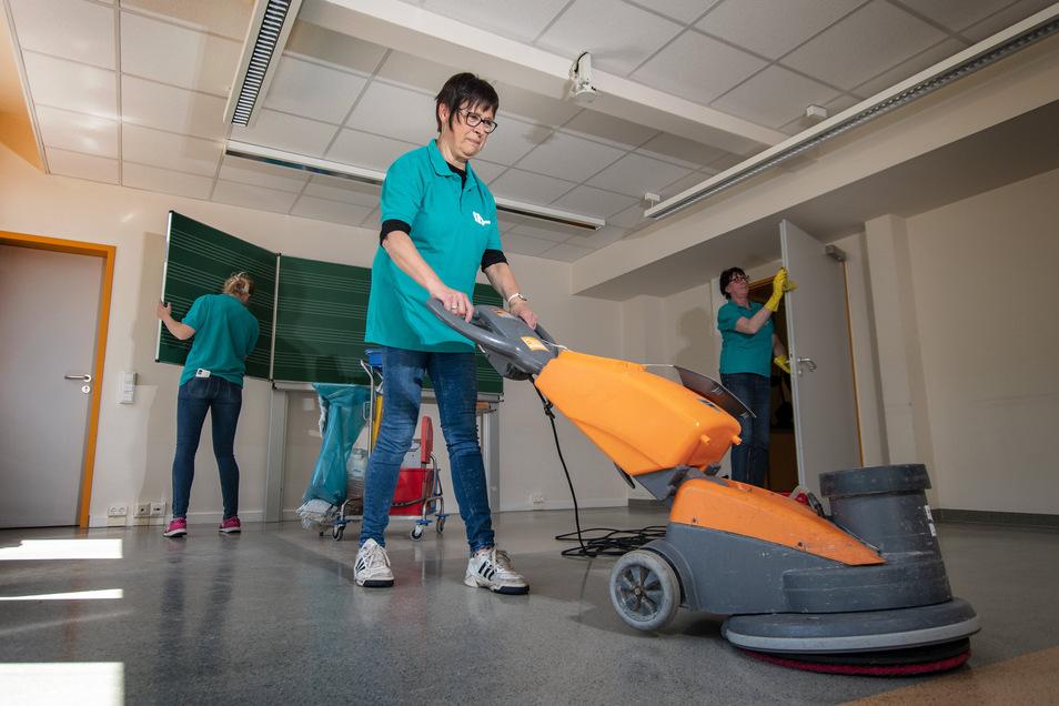 Gabriele Dähne von der Firma H&P Gebäudereinigung reinigt den Fußboden eines Klassenzimmers in der Grundschule Am Holländer mit einer Scheuermaschine.
