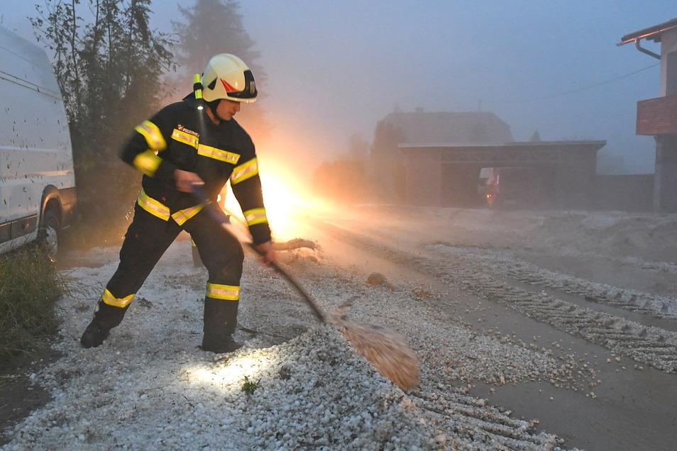 Österreich, Pinsdorf: Feuerwehrleute räumt Hagel zur Seite. In Österreich haben Unwetter mit großen Hagelkörnern zahlreiche Gebäude und Autos beschädigt.