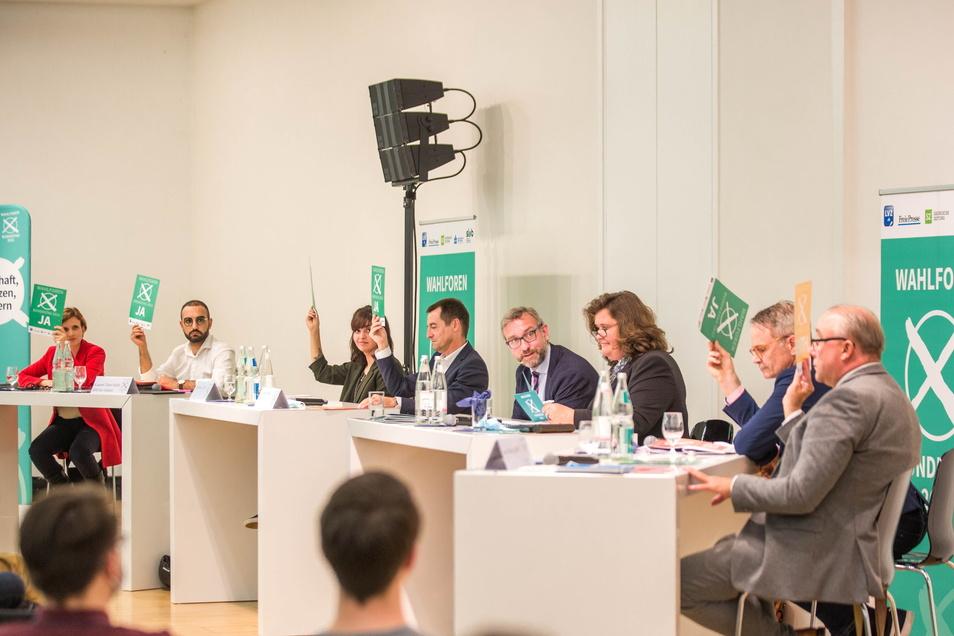 Im Forum sitzen v.l. Katja Kipping (Linke), Kassem Taher Saleh (Grüne), Rasha Nasr (SPD), Torsten Herbst (FDP), die Moderatoren Roland Löffler und Annette Binninger. Dazu Markus Reichel von der CDU und Jens Maier für die AfD.