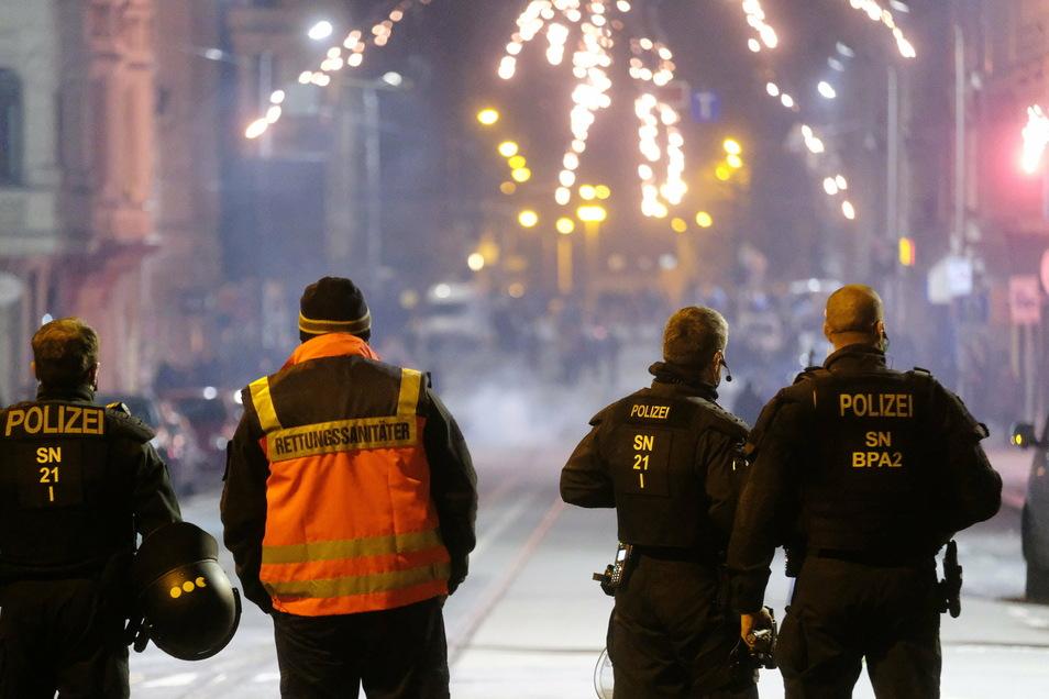 Polizisten und ein Rettungssanitäter stehen an einer Kreuzung in Leipzig. Die Stadt Leipzig hatte für die Silvesternacht Versammlungen verboten und in drei Zonen - darunter am Connewitzer Kreuz - ein Böllerverbot erlassen.