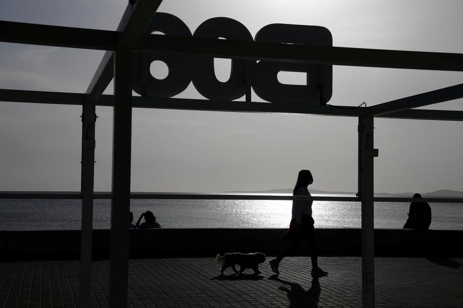 Eine Frau geht am geschlossenen Ballermann am Strand von Arenal in Mallorca vorbei.