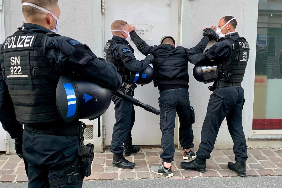 Polizisten halten einen Mann in Pirna fest, nachdem es dort bei einer Corona-Demo zu Gewalttätigkeiten gegen die Beamten kam.