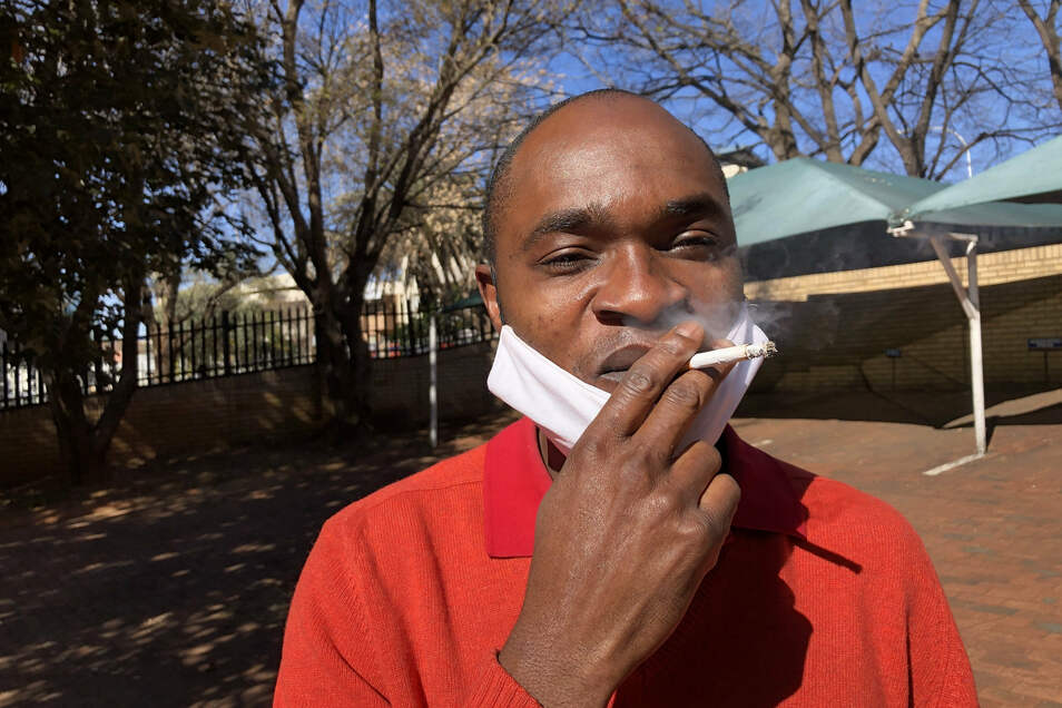 Pocha Ngulube zieht genüsslich an der Zigarette, die er für 5 Rand noch relativ günstig auf dem Schwarzmarkt erstanden hat.