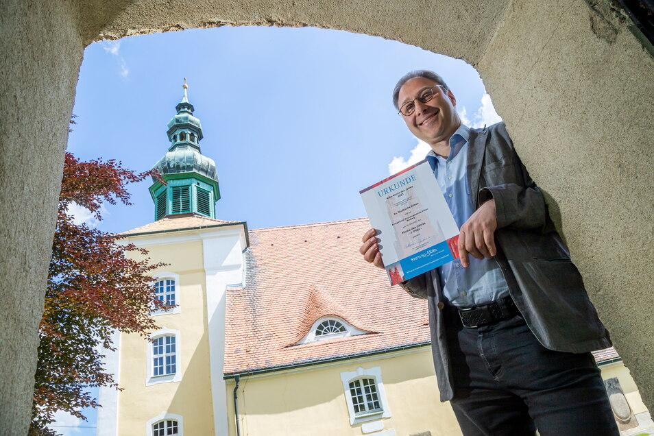 Pfarrer Daniel Jordanov steht vor der evangelischen Kirche in Klitten und zeigt die Urkunde für den dritten Platz im Wettbewerb der KiBa-Stiftung.