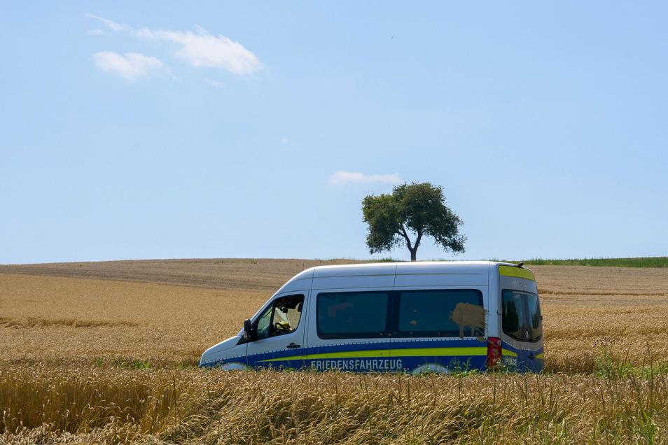 """Ein Transporter mit der Aufschrift """"Friedensfahrzeug"""" fährt am Rand des Katastrophengebiets in den Weinbergen entlang."""