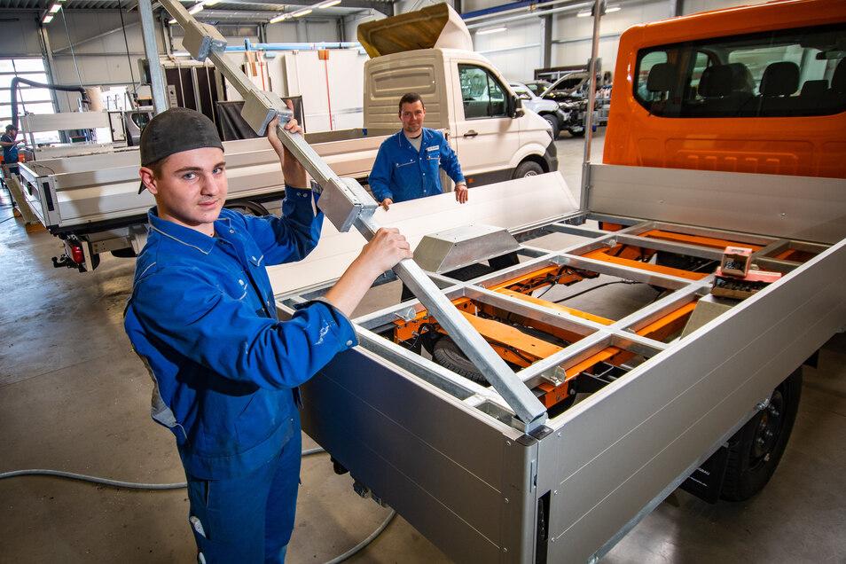Lehrling Luke Beyrich und Lehrmeister Kai Eichhorn (von links) montieren bei Kunath Fahrzeugbau in Roßwein den Zusatzaufbau an einem Kleinlaster.