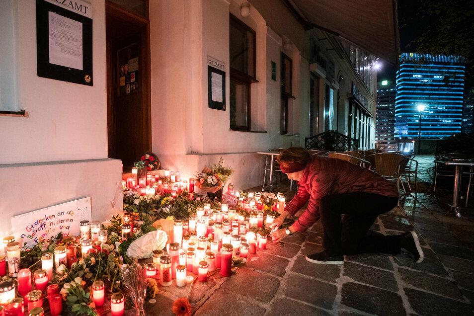 Eine Frau zündet eine Kerze am Tatort beim Ruprechtsplatz in der Wiener Innenstadt.