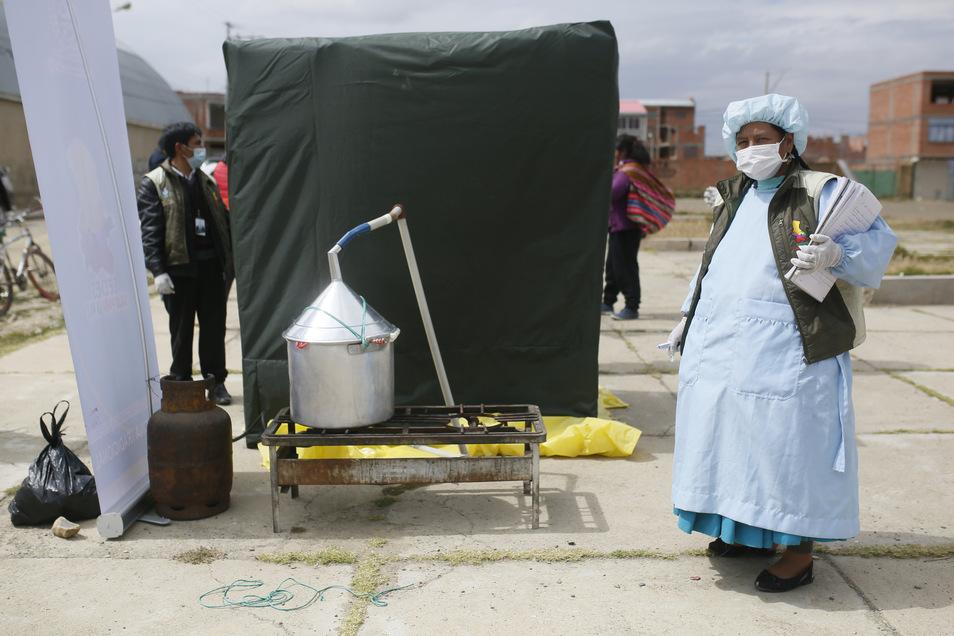 Bolivien, El Alto: Eine Mitarbeiterin des Ministeriums für Traditionelle Medizin steht in Schutzanzug neben einer Dampfkabine, die während der Corona-Pandemie zur Vorbeugung von Erkrankungen der Atemwege an einer Ecke aufgestellt wurde.