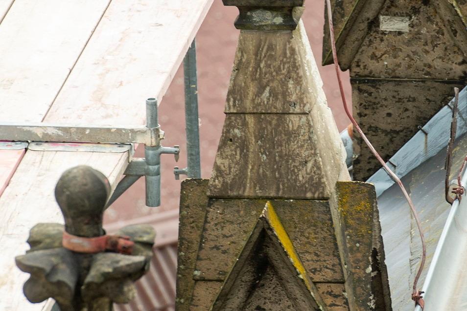Kreuzblumen aus Sandstein schmücken die Ränder des Kirchendaches. Saurer Regen hat diese angefressen.