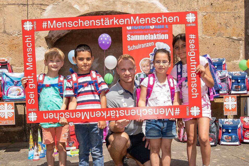 Ranzenspende-Aktion der Caritas Pirna mit Schirmherr Francesco Friedrich (Mitte): Hilfe für bedürftige Kinder.