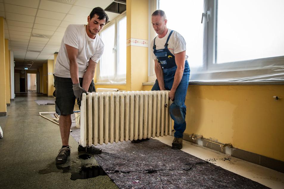 Amaju Iqball und Andreas Koppisch von der Firma Heizungstechnik Waldheim demontieren alte Heizkörper aus Gusseisen. Diese stammen aus dem Jahr des Schulbaus.