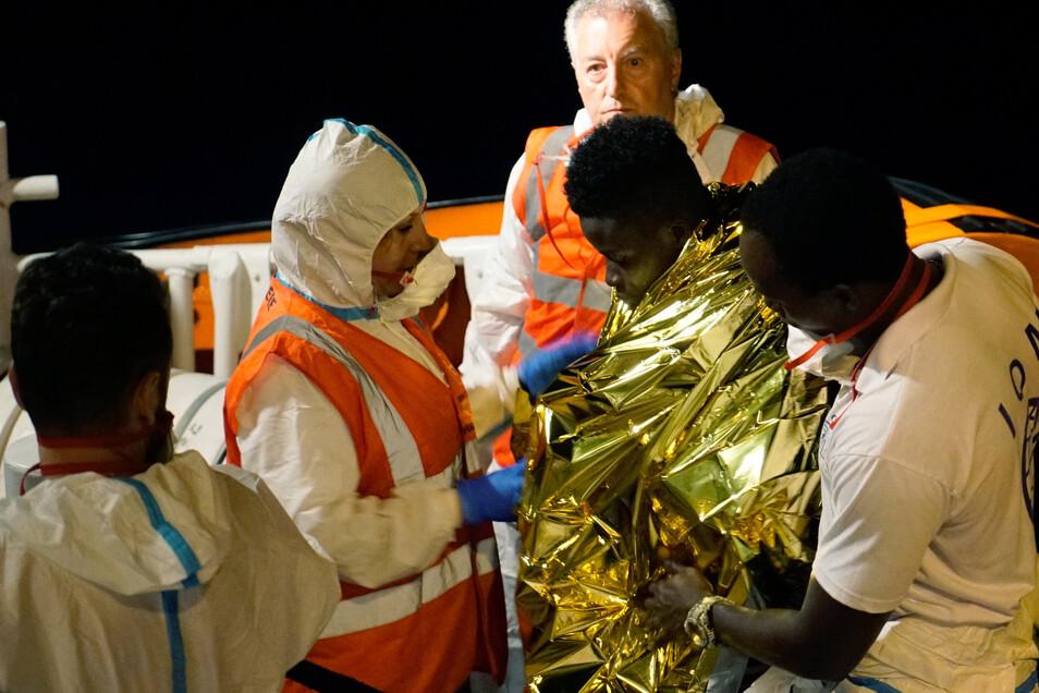 """Besatzungsmitglieder kümmern sich um einen erkrankten Flüchtling an Bord des deutschen Rettungsschiffes """"Sea Watch 3""""."""