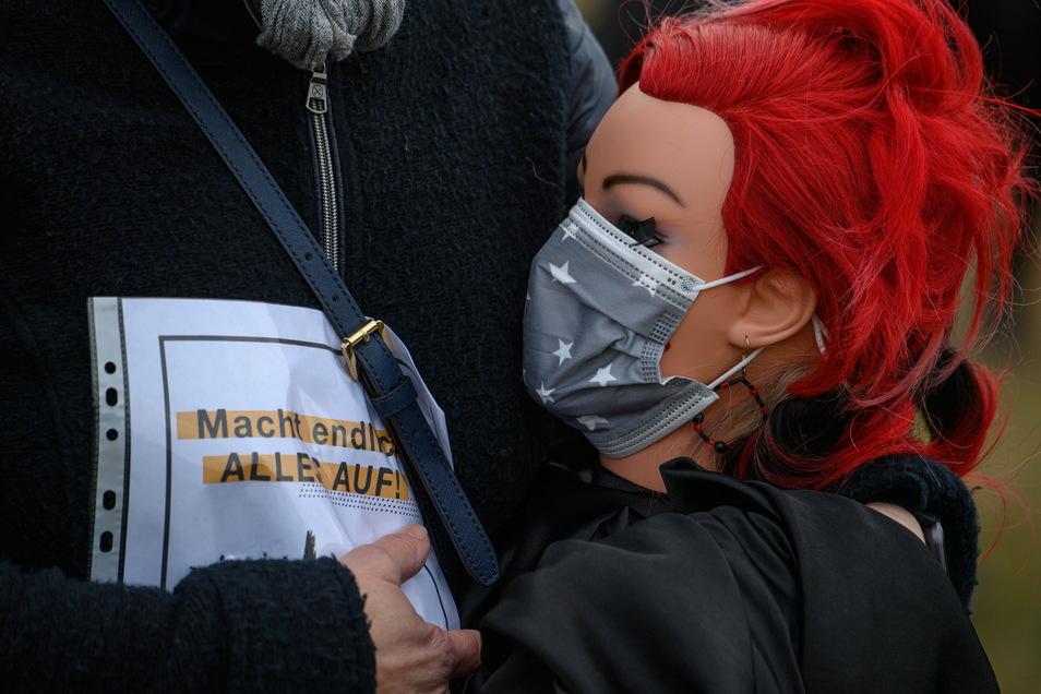 """Eine Teilnehmerin der Protestaktion hält eine Frisierpuppe mit Mundschutz und einem Zettel mit der Aufschrift """"Macht endlich alles auf"""" in den Händen."""