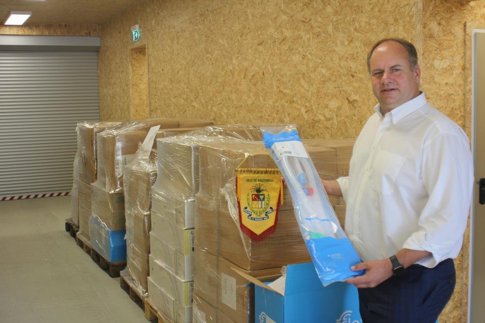 Oberbürgermeister Dirk Hilbert vor der transportfertig verpackten Lieferung für die Partnerstadt Brazzaville. In der Hand hält er ein Schlauchsystem für Atembeutel.