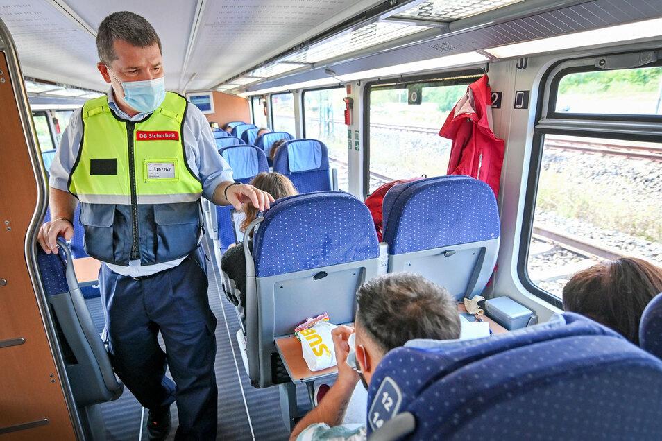 Lutz Fuge (l) vom Präventionsteam der Deutschen Bahn kontrolliert in einem Zug das Tragen von Mund-Nasen-Bedeckungen bei den Fahrgästen.