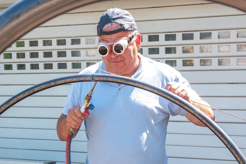 Holger Krüger schweißt die Enden eines der gebogenen Rohre zusammen, damit daraus ein Ring wird.