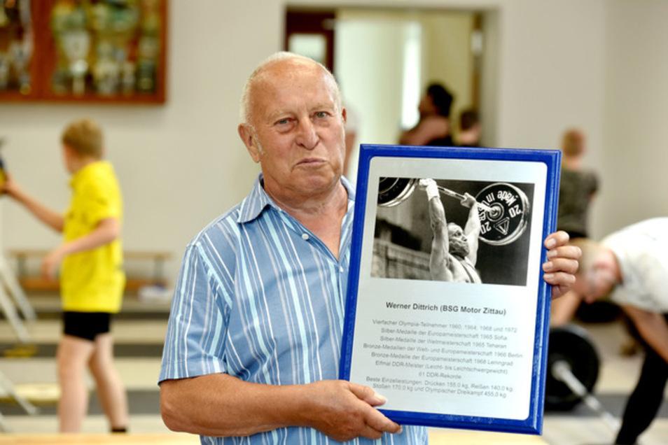 Der Namensgeber Werner Dittrich mit der Tafel, die in der Halle angebracht wird.