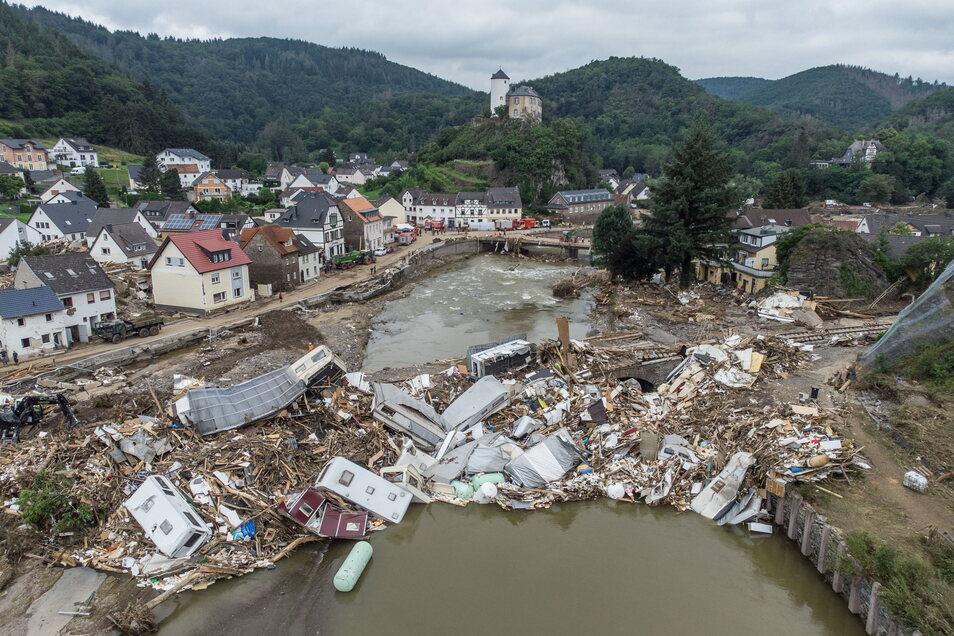 Am 19. Juli zeigt diese Luftaufnahme die Gemeinde Altenahr in Rheinland-Pfalz. Meterhoch türmen sich Wohnwagen, Gastanks, Bäume und Schrott an einer Brücke über die Ahr. Viele Häuser im Ort wurden komplett zerstört oder stark beschädigt, und es gab