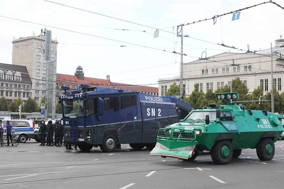 Ein Wasserwerfer und ein Räumfahrzeug der Polizei stehen auf dem Augustusplatz.