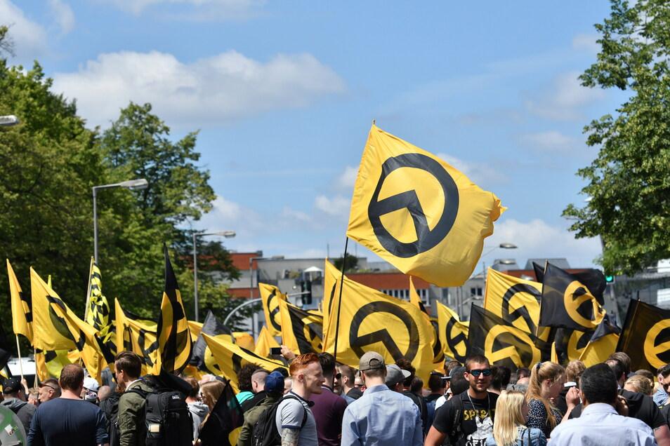 """Anhänger der """"Identitären Bewegung"""" stehen mit ihren Fahnen in Berline. Das Bundesamt für Verfassungsschutz (BfV) darf die Bewegung weiter als """"gesichert rechtsextremistisch"""" bezeichnen."""