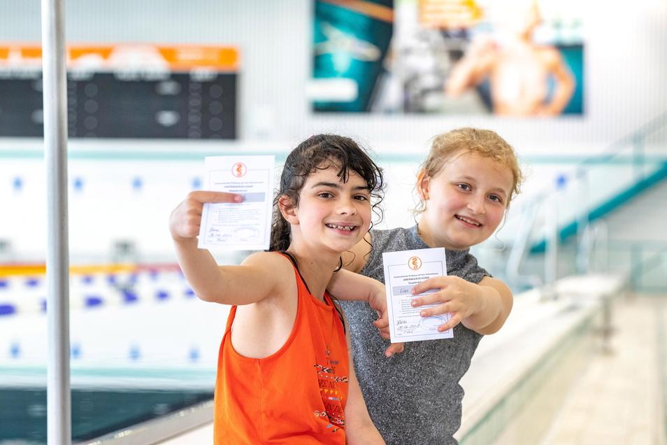 Zwei der erfolgreichen Schwimm-Schulkinder zeigen im Riesaer Bad ihr frisch erworbenes Seepferdchen.