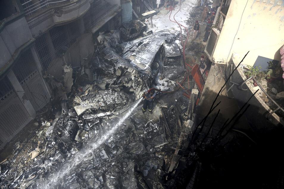Ein Feuerwehrmann versucht das Feuer an der Absturzstelle zu löschen.