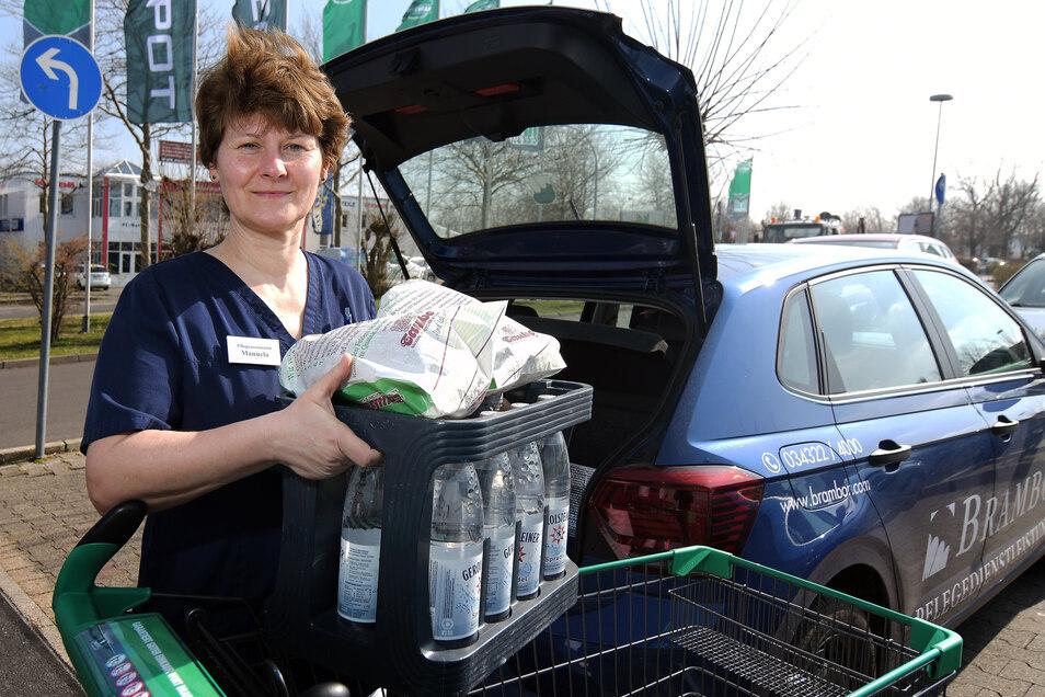 Manuela Ehrt vom Pflegedienst Brambor packt eine Kiste Mineralwasser und weitere Einkäufe ins Auto. Sie geht regelmäßig für Klienten einkaufen.
