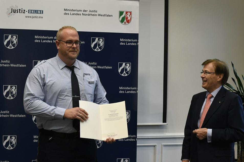 Peter Biesenbach (CDU, r),  Justizminister von Nordhein-Westfalen, bedankt sich bei Daniel Freihoff (l) mit einer Urkunde für seinen Einsatz. Anfang September auf der Autobahn.