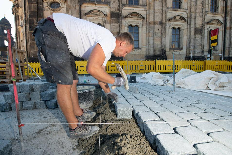 Straßenbauer Sven Eichler von der Firma Hausdorf setzt die neuen, geschnittenen Steine an der Haltestelle vor der Hofkirche. Diesen Belag erhält auch die Fahrbahn mit den Radwegen auf der Augustusbrücke.