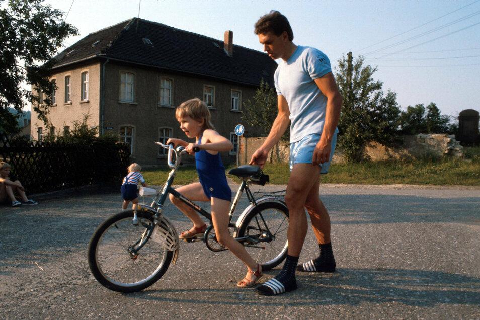Mitte der Achtziger: Radrennfahrer Olaf Ludwig hilft Tochter Madlen beim Gleichgewichthalten. Er hat die DDR bewusst erlebt, sie nicht mehr. Viele jüngere Ostdeutsche wissen nichts über das Leben vor 1989. Das liegt oft an der Scheu vor dem Fragen.