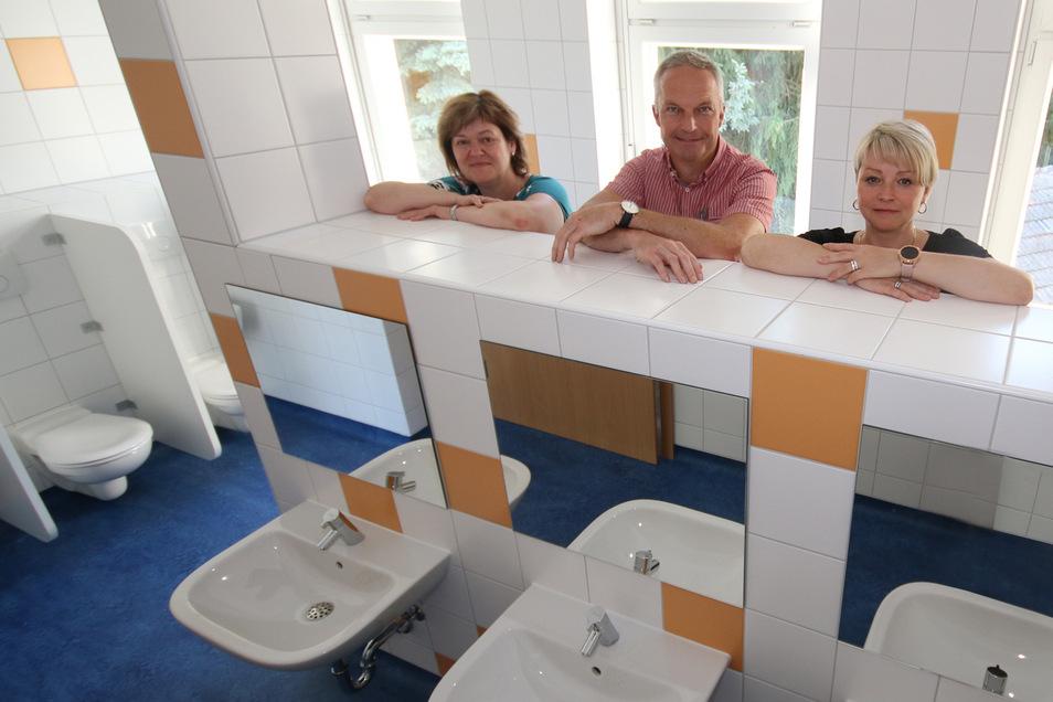Andrea Winkler, Gebietsleiterin der Ostrauer Kindertagesstätten, Bürgermeister Dirk Schilling, und Kati Staats, Leiterin der Kita Sonnenkinder (von links), sehen sich den neuen Sanitärraum der Kiebitzer Einrichtung an.
