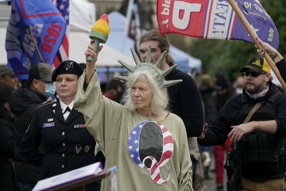 Eine Person, die als Lady Liberty gekleidet ist, trägt ein Hemd mit dem Buchstaben Q, der sich auf QAnon bezieht, als Demonstranten an einem Protest teilnehmen, am Kapitol in Olympia, Wash. Die Demonstranten protestierten gegen die Auszählung der Wahlmänn