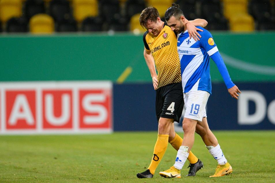 Das Bild zum Spiel: Innenverteidiger Knipping humpelt vom Platz, gestützt von Darmstadts Torjäger Dursun, der das 3:0 erzielt hat.