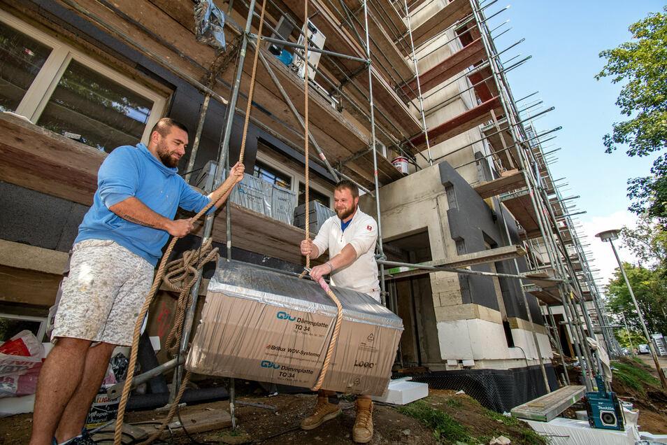Daniel Warschkow (links) und Rico Frischholz befestigen Dämmmaterial an einem Aufzugsseil.