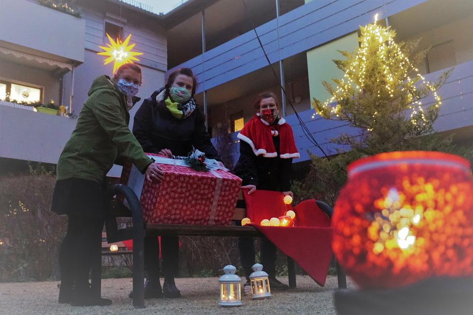 """Übergabe mit Abstand: Das Leitungsduo Romy Reiser (Mitte) und Ariane Stransfeld (l.) vom Weinböhlaer VS-Hort """"Kreativ"""" übergibt in Coswig eine große Geschenkbox mit rund 100 Basteleien an VS-Wohnanlagenleiterin Silke Krause."""