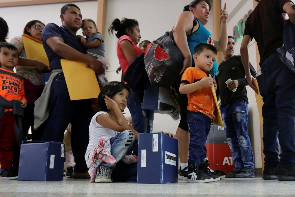 USA, Mcallen: Asylsuchende Immigranten stehen in einer Reihe an einer Bushaltestelle, nachdem sie vom US-Grenzschutz zuvor erfasst und und ihre Einreise genehmigt worden war.